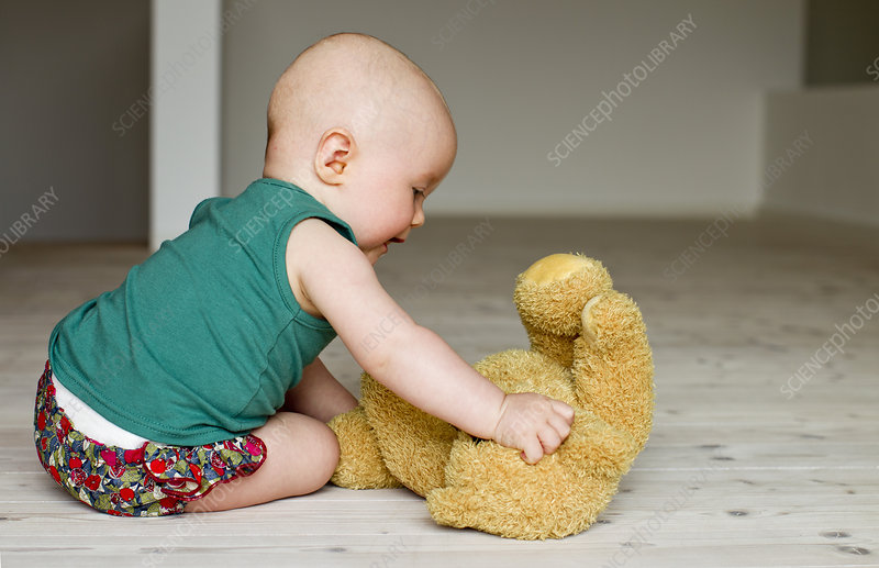 Baby girl playing with teddy bear