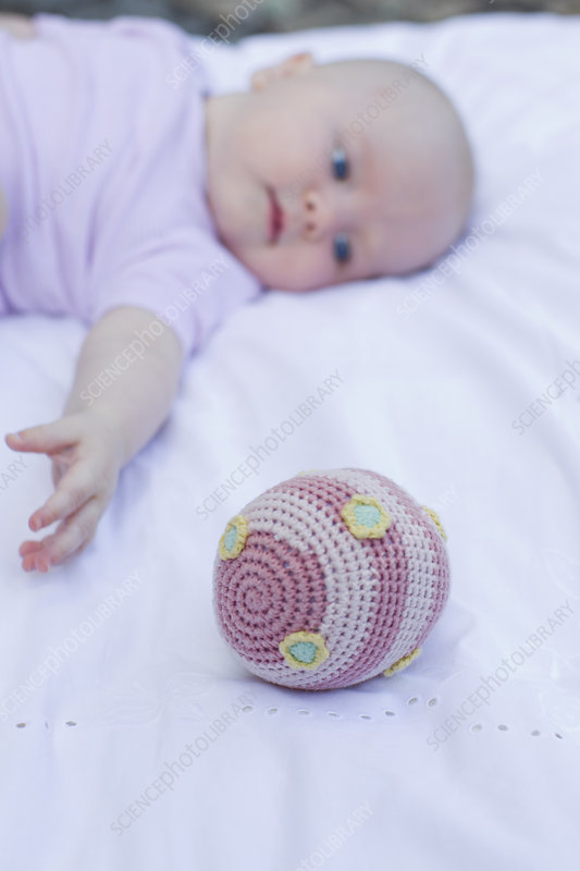 Baby girl reaching for ball