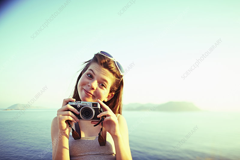 Girl holding camera on holiday