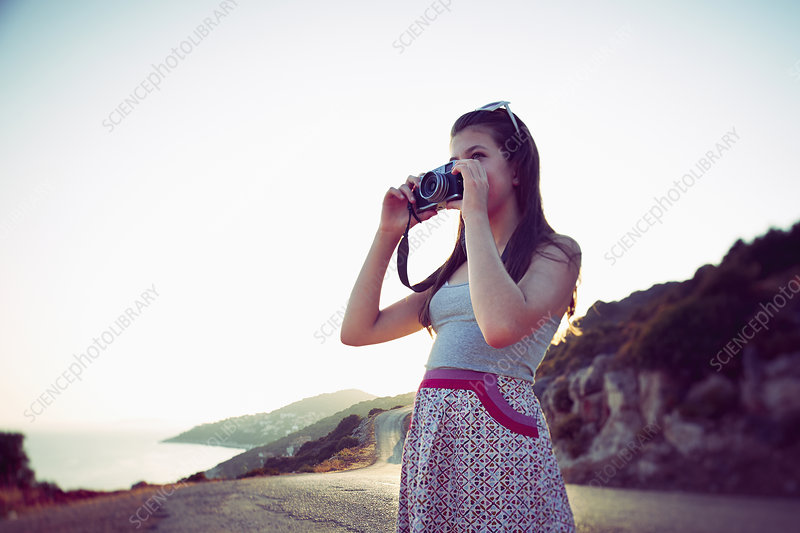 Girl taking photographs at dusk