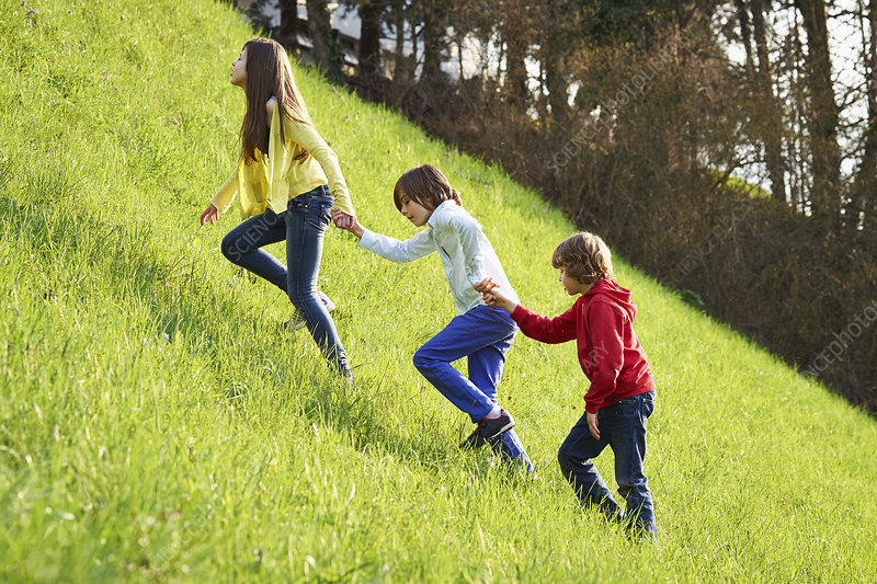 Siblings climbing up grassy field