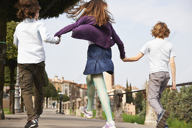 Siblings marching through park, Italy