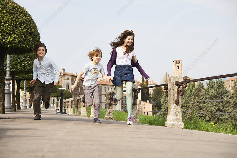 Siblings running through park, Italy