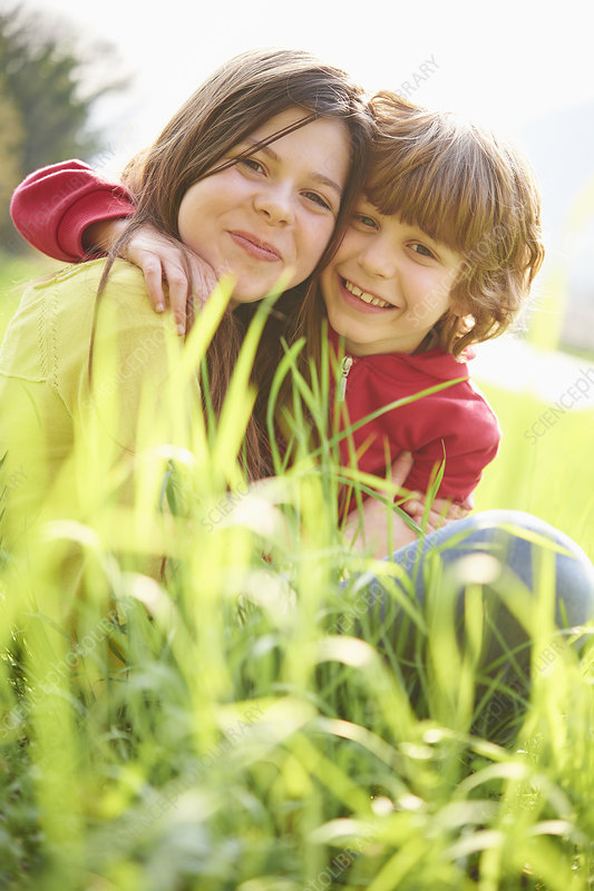Siblings sitting in grassy field