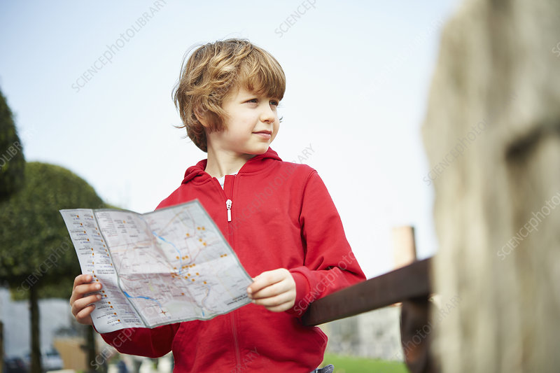Young boy holding map in park, Italy