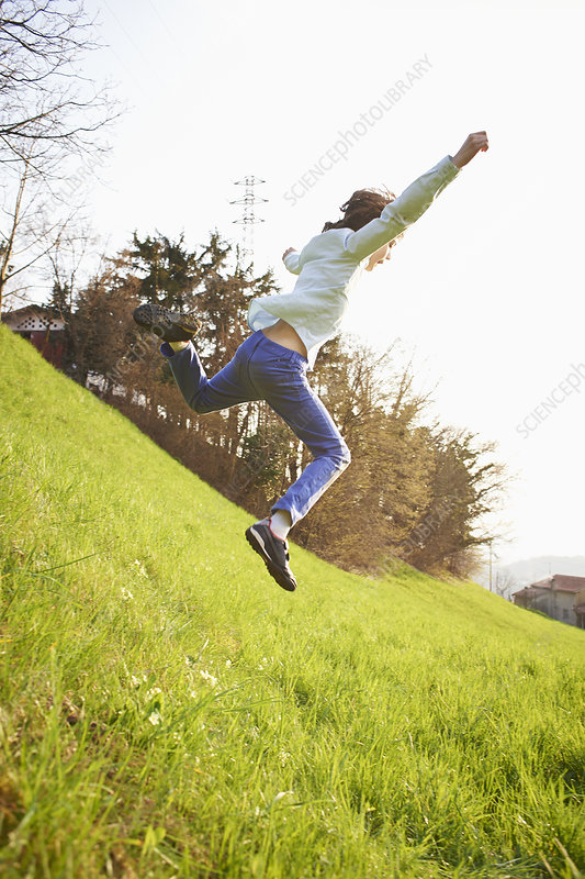Young boy jumping down steep grassy field