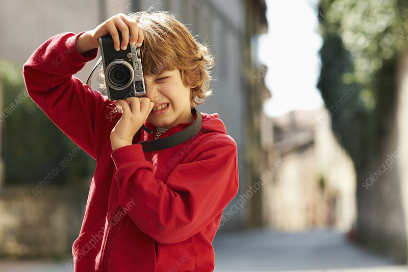 Young boy photographing on street, Italy