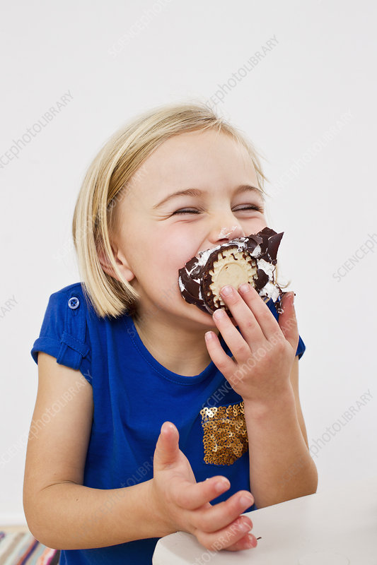 Young girl eating chocolate marshmallow