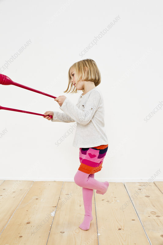 Young girl juggling on one leg