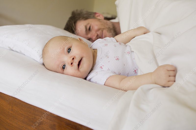 Father and baby daughter on bed