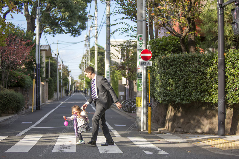 Father and daughter on zebra crossing
