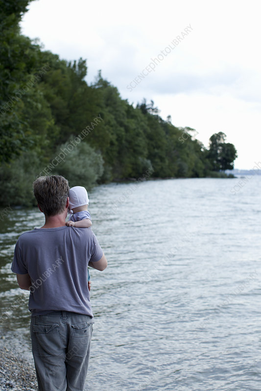 Father holding baby daughter by lake