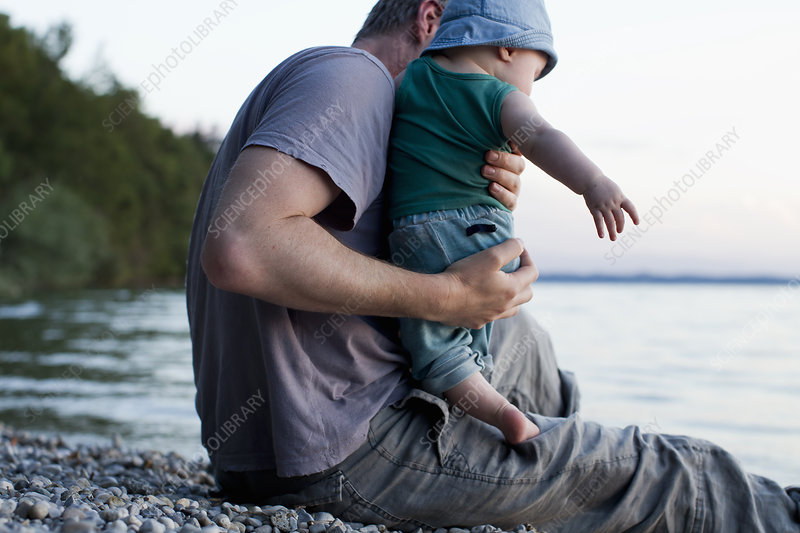 Father with baby daughter by lake