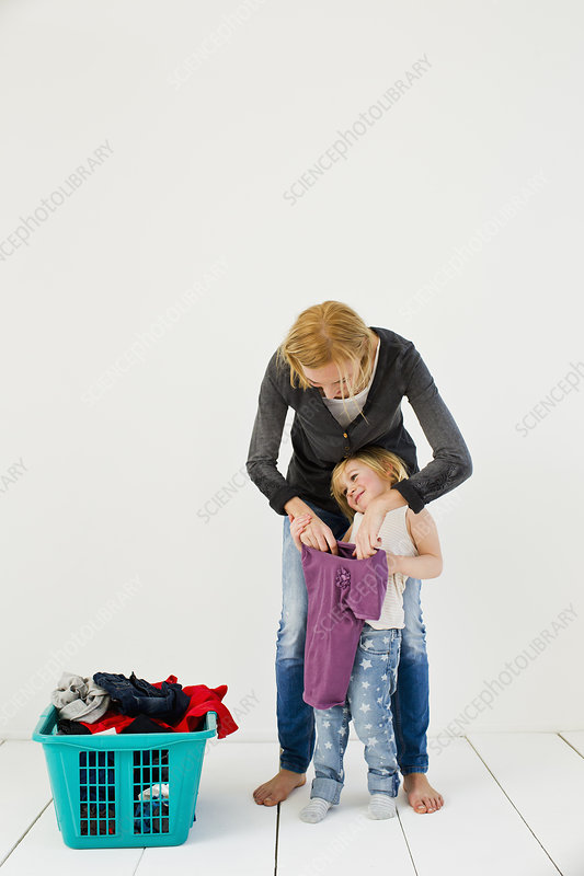 Mother and daughter with dirty laundry
