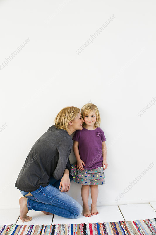 Mother kneeling next to young daughter
