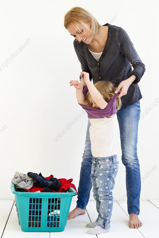 Mother taking off daughter's clothes
