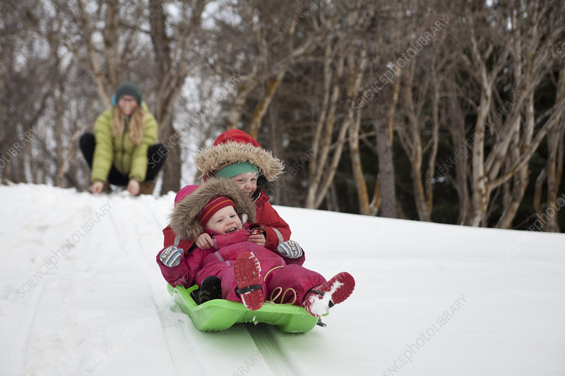 Mother watching daughters sledging