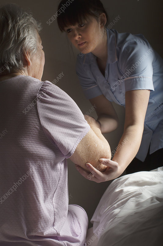 Carer helping senior woman to get up