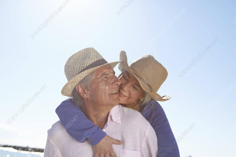 Couple wearing straw hats on beach