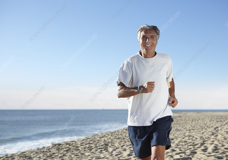 Senior man jogging on beach
