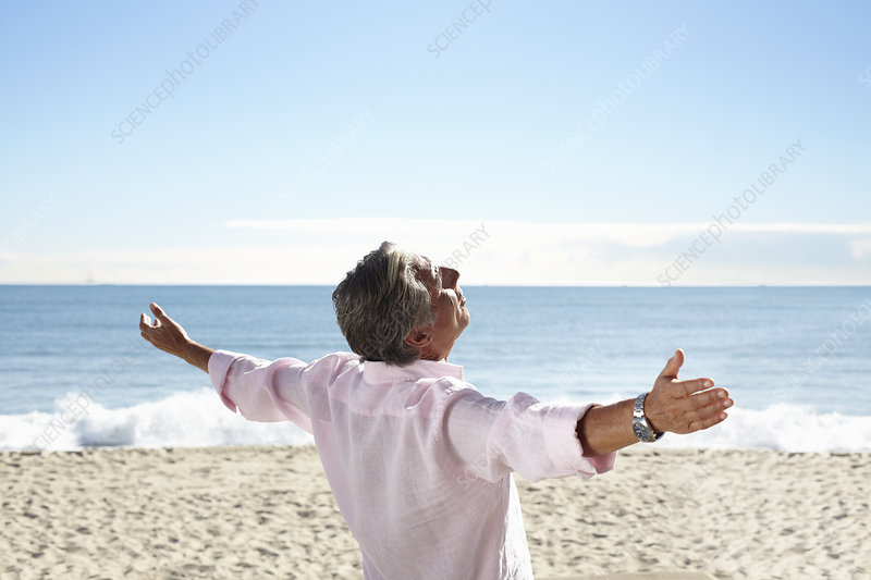Senior man on beach with arms outspread