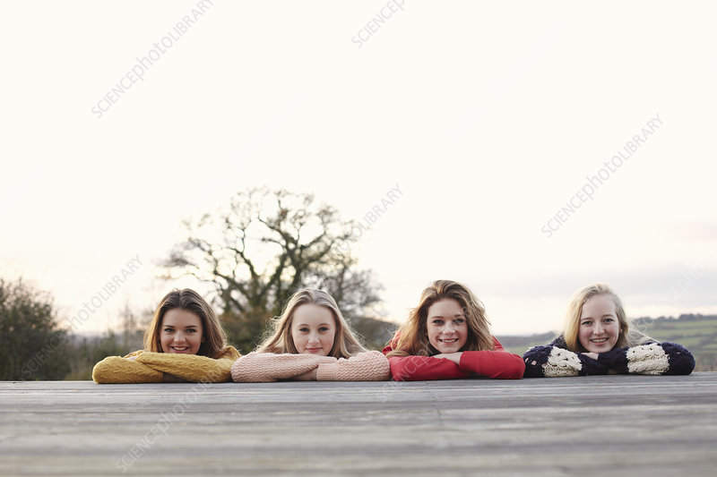 Four teenage girls in a row on patio