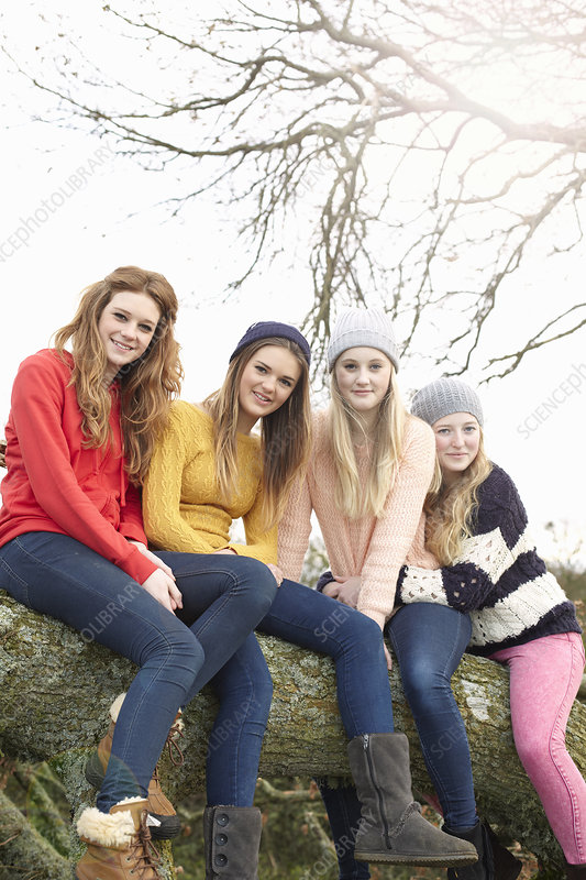 Four teenage girls sitting on tree trunk
