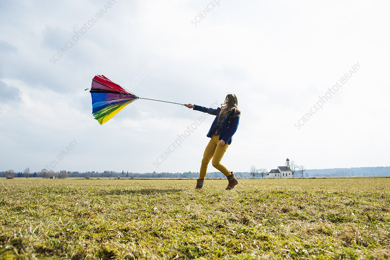 Teenage girl in field with umbrella