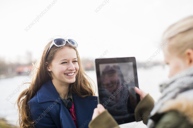 Teenage girl photographing friend