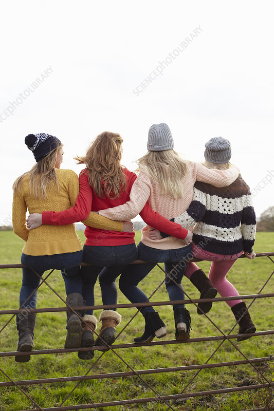 Teenage girls sitting on gate