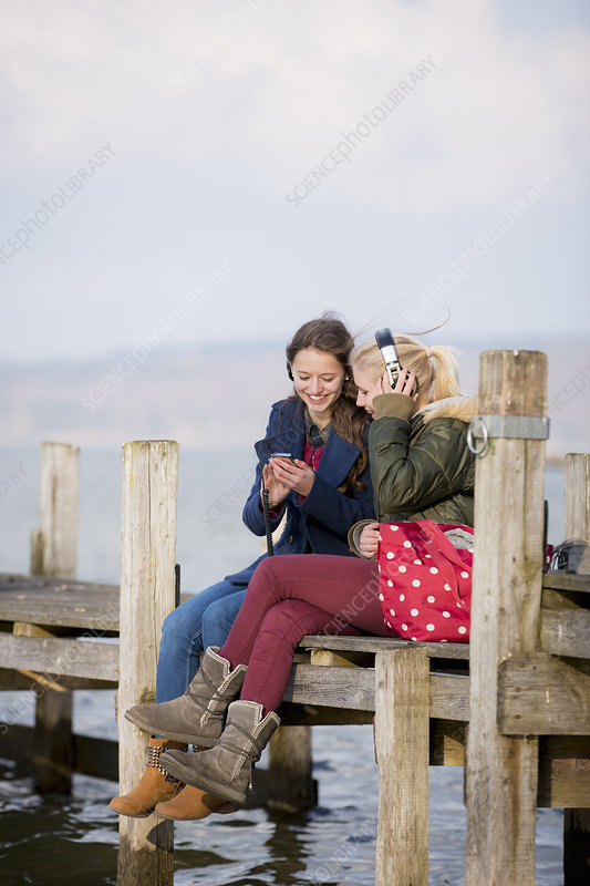 Teenage girls sitting on jetty