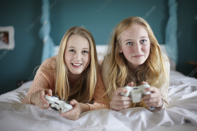 Two teenage girls playing computer game