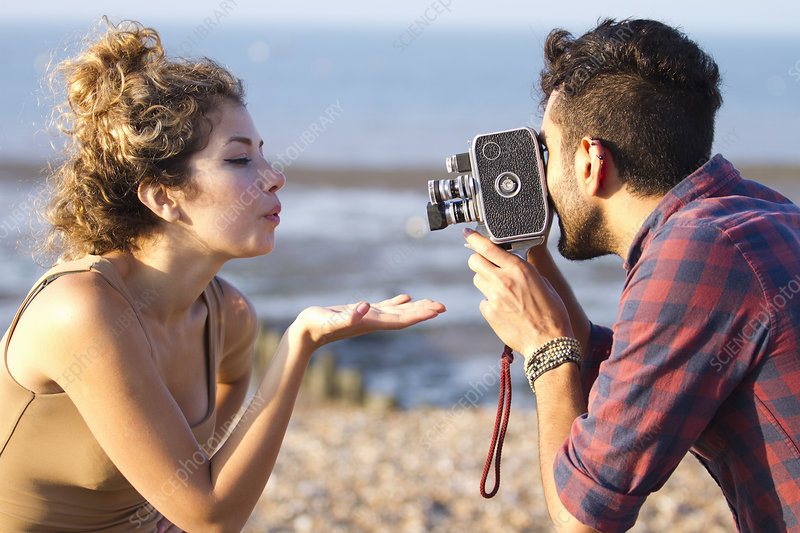 Man filming woman with vintage camera