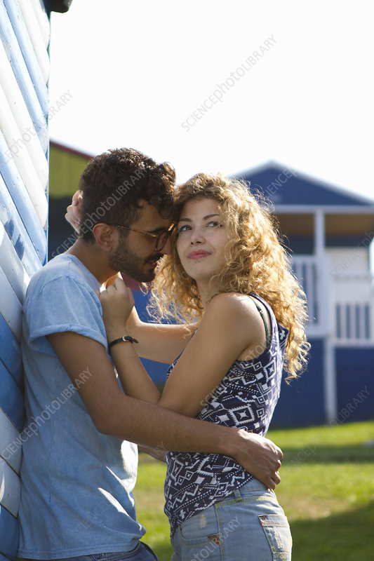 Young couple hugging by beach hut