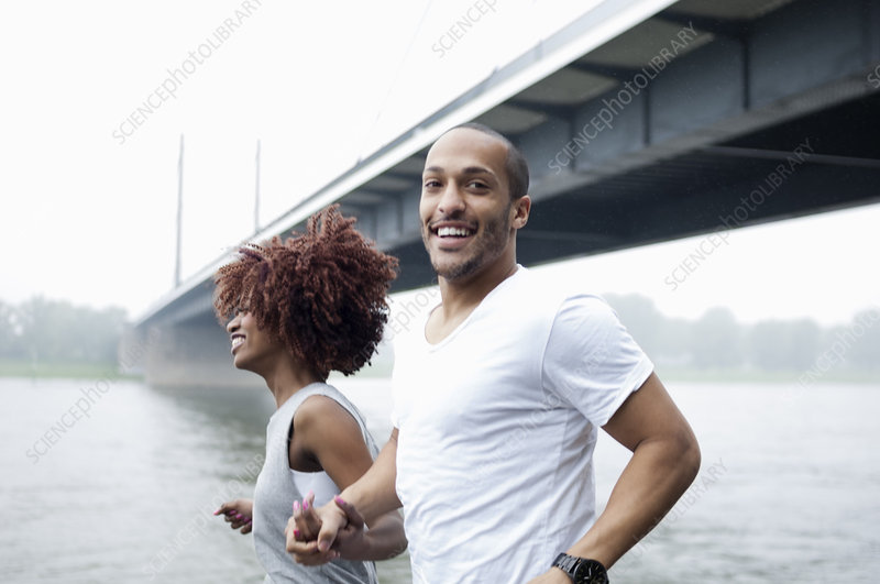 Young couple jogging by bridge