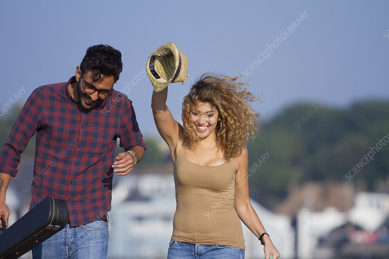 Young couple laughing, woman holding hat