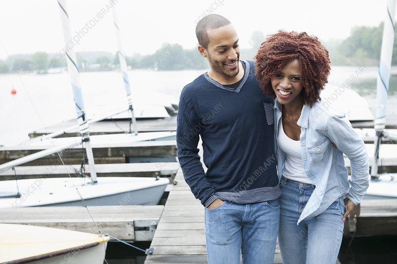 Young couple on jetty laughing