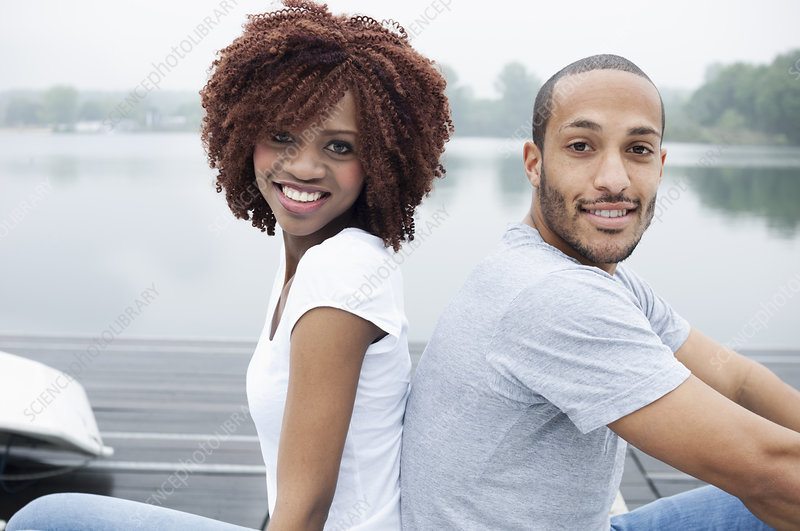 Young couple smiling, back to back