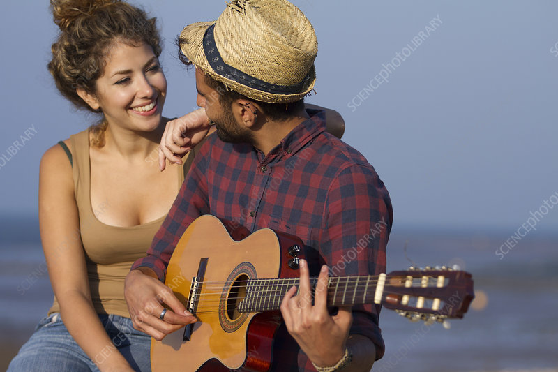 Young couple, man playing guitar
