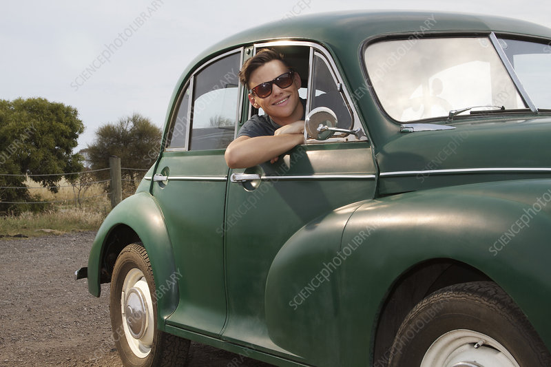 Young man in vintage morris minor