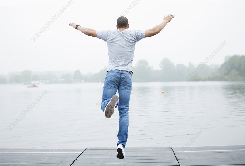 Young man jumping into lake