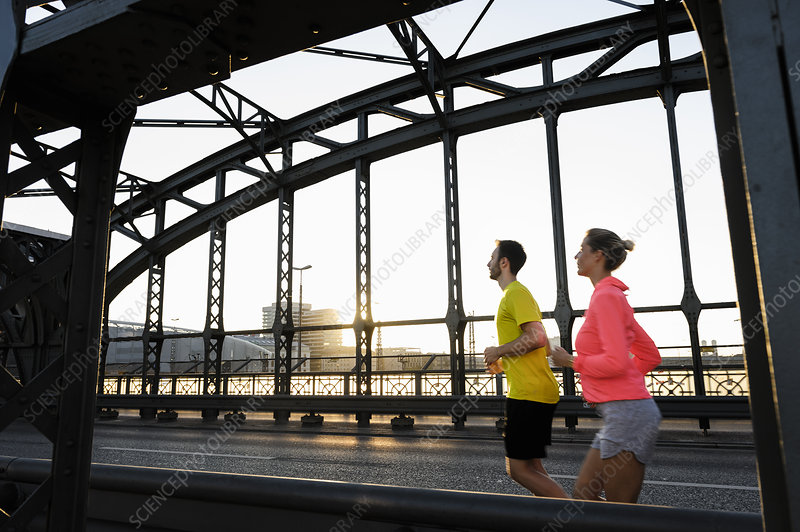 Male and female runners crossing bridge