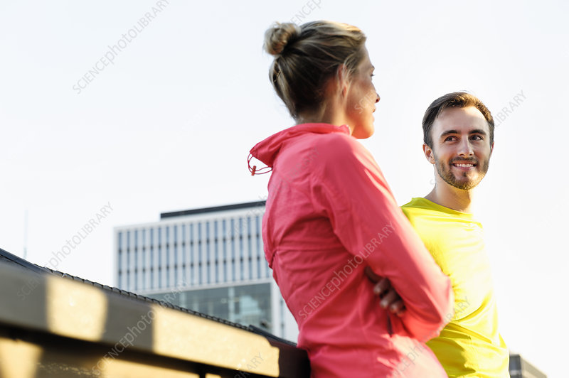 Male and female runners talking on bridge