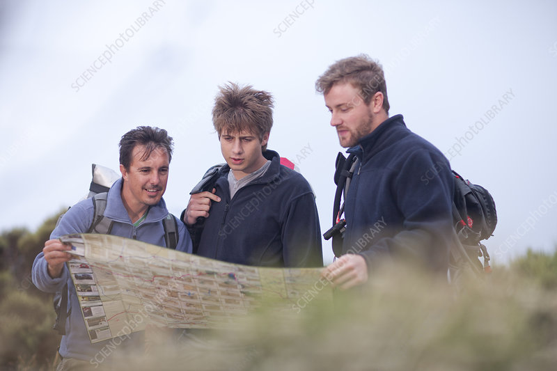 Male hikers looking at map