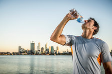 Male runner drinking water