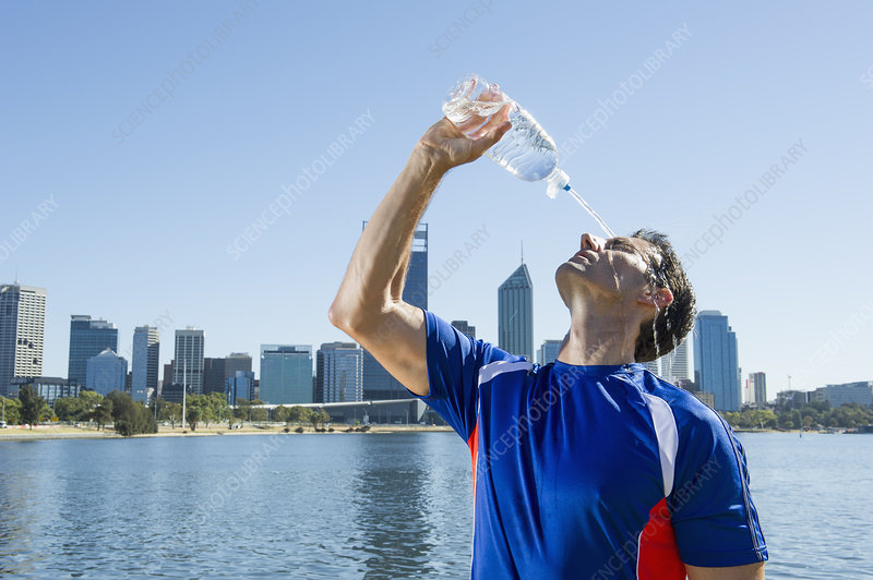 Male runner pouring water over his face