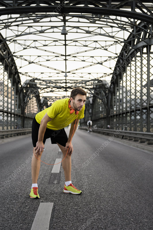 Male runner taking a break on bridge