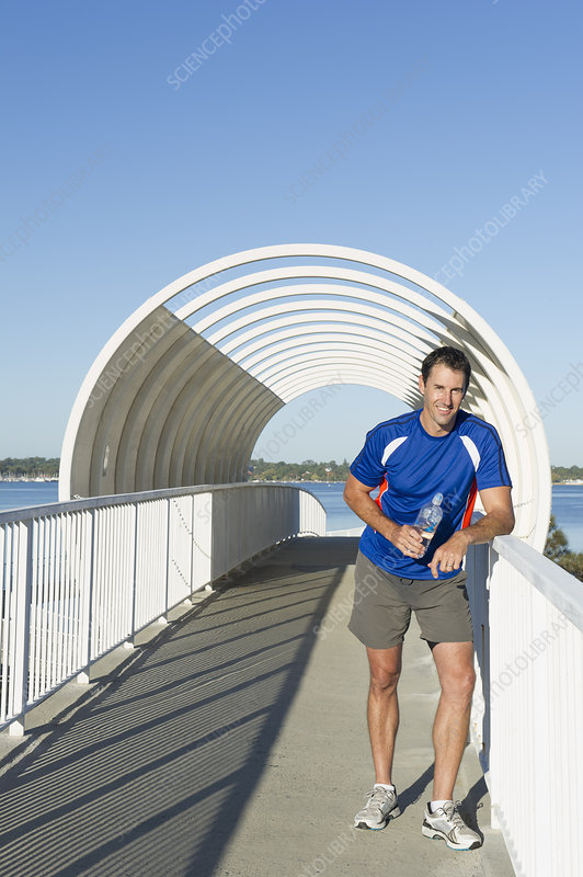 Male runner taking a break on footbridge