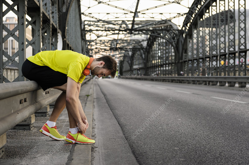 Male runner tying shoelace on bridge
