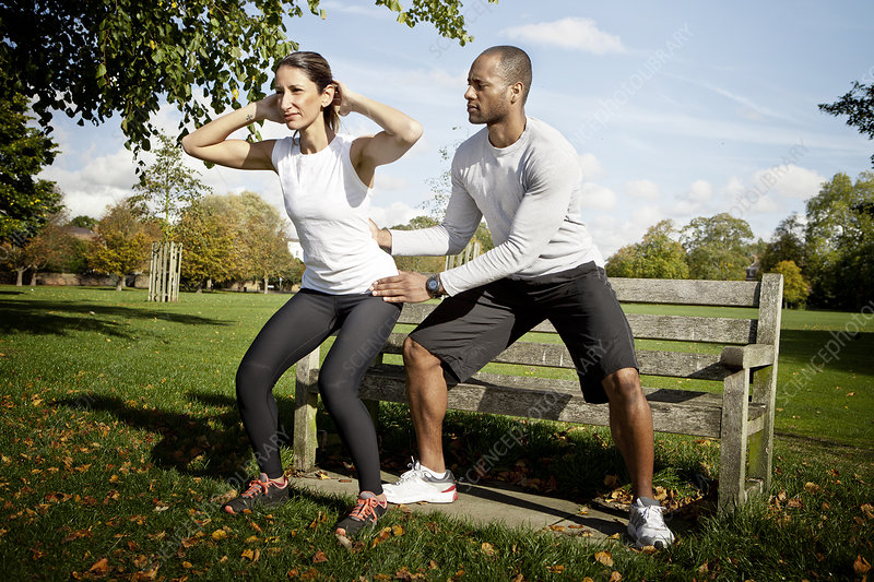 Man guiding woman doing squats in park